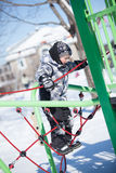 Boy in a playground in winter Stock Photos