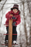 Boy on the playground, winter day. Young boy plays  outdoor at winter playground Royalty Free Stock Photos