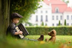 A boy playing accordion. A four years old boy sitting on grass and play accordion for teddy bear royalty free stock images