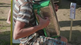 Boy playing accordion sitting on chair outdoors stock footage
