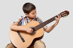 Boy is playing the acoustic guitar Stock Image