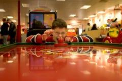 Boy Playing Air Hockey. Photo of a silly boy playing air hockey at an arcade Stock Photos