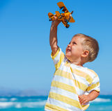 Boy playing with airplane Stock Images