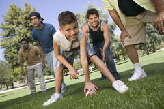 Boy Playing American Football With Group Of Men. Portrait of a young boy playing American football with group of men in the park Royalty Free Stock Image