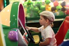 Boy playing arcade game machine. At an amusement park Royalty Free Stock Image