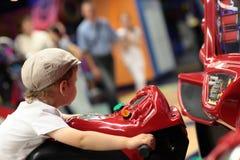 Boy playing arcade simulator machine. At an amusement park Royalty Free Stock Photos