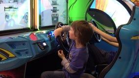 Boy playing auto simulator video arcade game. Moscow, Russia - March, 2017: Boy playing auto simulator video arcade game stock video