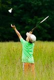Boy playing badminton. Young boy playing badminton in a meadow with a forest in background Royalty Free Stock Image