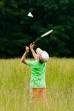 Boy playing badminton. Young boy playing badminton in a meadow with a forest in background Royalty Free Stock Photos