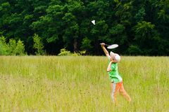 Boy playing badminton. Young boy playing badminton in a meadow with a forest in background Stock Photos