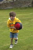 Boy playing with ball. Outdoor portrait of boy playing with basketball Stock Image