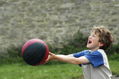 Boy playing with ball. Outdoor portrait of boy playing with basketball Royalty Free Stock Images