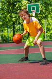 Boy playing with ball alone during basketball game. Outside during sunny summer day Royalty Free Stock Photography