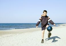 Boy playing ball on beach. A boy kicking a ball on a beach, wearing a sweatshirt, the ball frozen above the ground Stock Images
