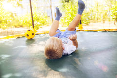 Boy playing with a ball, jumping on a trampoline. Happy teenager boy plays outdoors in garden jumping high in the sky on trampoline stock image