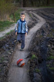 Boy playing with a ball on the mud road Stock Photography