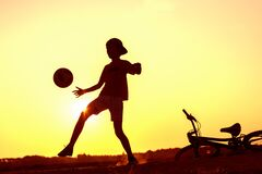 Boy playing with ball in nature, bicycle lies nearby