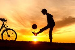 Boy playing with ball in nature, bicycle nearby