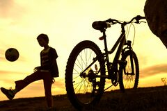 Boy playing with ball in nature, bicycle stands nearby
