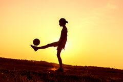 Boy playing with ball in nature in hot evening