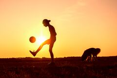 Boy playing with ball in nature in hot evening, dog nearby