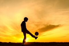 Boy playing with ball in nature, silhouette of playing child