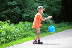 Boy playing with ball in park outdoors Stock Images