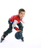 Boy playing ball on the roller-skates Stock Photography