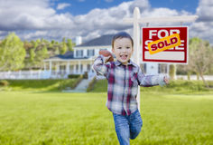 Boy Playing Ball in Yard Near Sold Real Estate Sign Royalty Free Stock Images