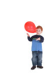 Boy playing with balloon. Young boy catching and throwing balloon isolated on white Stock Photo