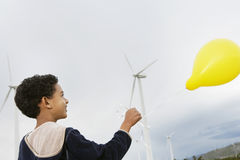 Boy Playing With Balloon At Wind Farm. African American little boy playing with yellow balloon at wind farm Royalty Free Stock Photo