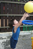 Boy playing basket ball. Little boy in blue singlet playing basket ball royalty free stock images