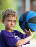 Boy playing basketball. Boy holding up basketball getting ready to shoot Royalty Free Stock Photo