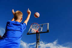 Boy playing basketball. Outside with blue sky in background Stock Images