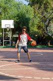 The boy is playing basketball alone stock photos