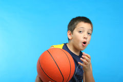 Boy playing basketball. Blue background Royalty Free Stock Photo