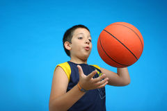 Boy playing basketball. blue background Royalty Free Stock Image