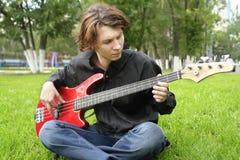 Boy playing the bass guitar stock photos