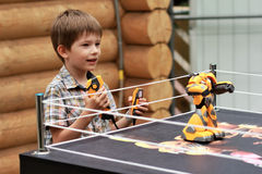 Boy playing battle fighting robot with remote control royalty free stock image