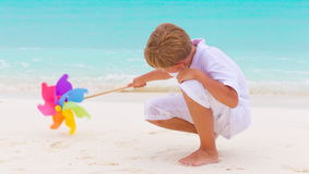 Boy playing on beach. Young boy playing with colorful windmill on sandy beach, sea in background Stock Images