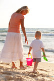Boy playing on the beach. Boy playing with grandmother on the golden beach Royalty Free Stock Photo