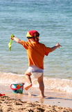 Boy playing on beach. Boy playing with shovel and bucket at water's edge at beach stock photography