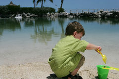 Boy playing at the beach. A view of a young boy playing with a plastic pail and shovel in the sand at the beach Stock Photo