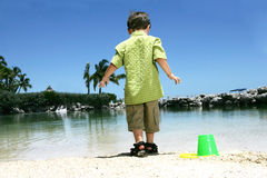 Boy playing on beach. A view of a young boy playing in the sand on a beach and standing at the water's edge on a bright sunny day Royalty Free Stock Photos
