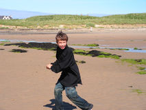 Boy playing on the beach. A smiling boy running around the beach with a handful of sand pretending to play snowballs Royalty Free Stock Photos