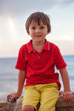 Boy, playing on the beach in the evening after rain with toys. Rainbow behind him Stock Photos
