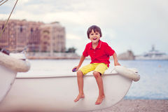 Boy, playing on the beach in the evening after rain with toys Royalty Free Stock Photography