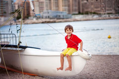 Boy, playing on the beach in the evening after rain with toys Royalty Free Stock Photo