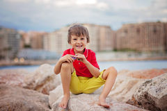 Boy, playing on the beach in the evening after rain with toys Stock Photography