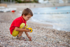 Boy, playing on the beach in the evening after rain with toys Stock Image